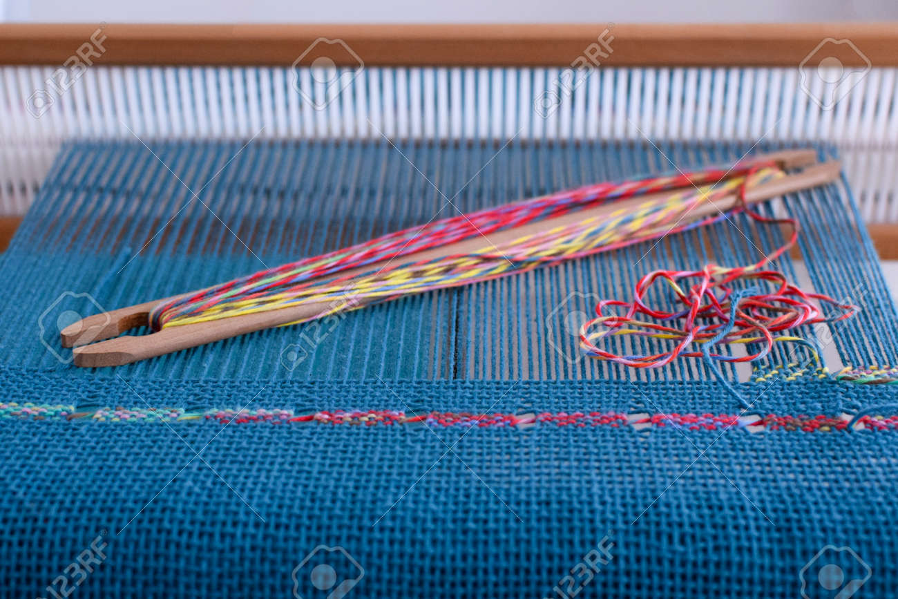 Spanish lace weaving on rigid heddle loom with blue warp and colorful weft - 104022454