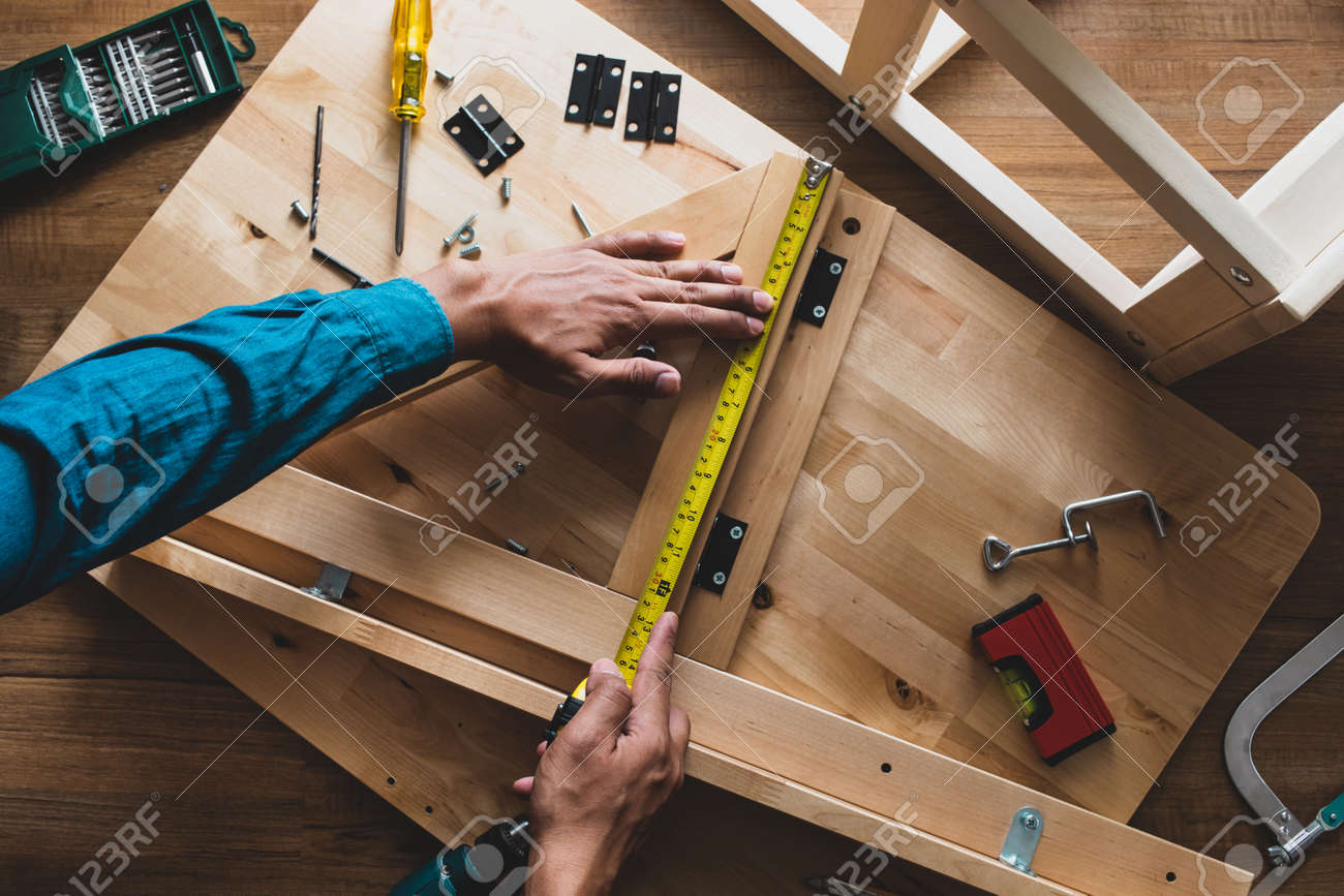 Man assembly wooden furniture,fixing or repairing house with yellow tape measures.top view - 118040738