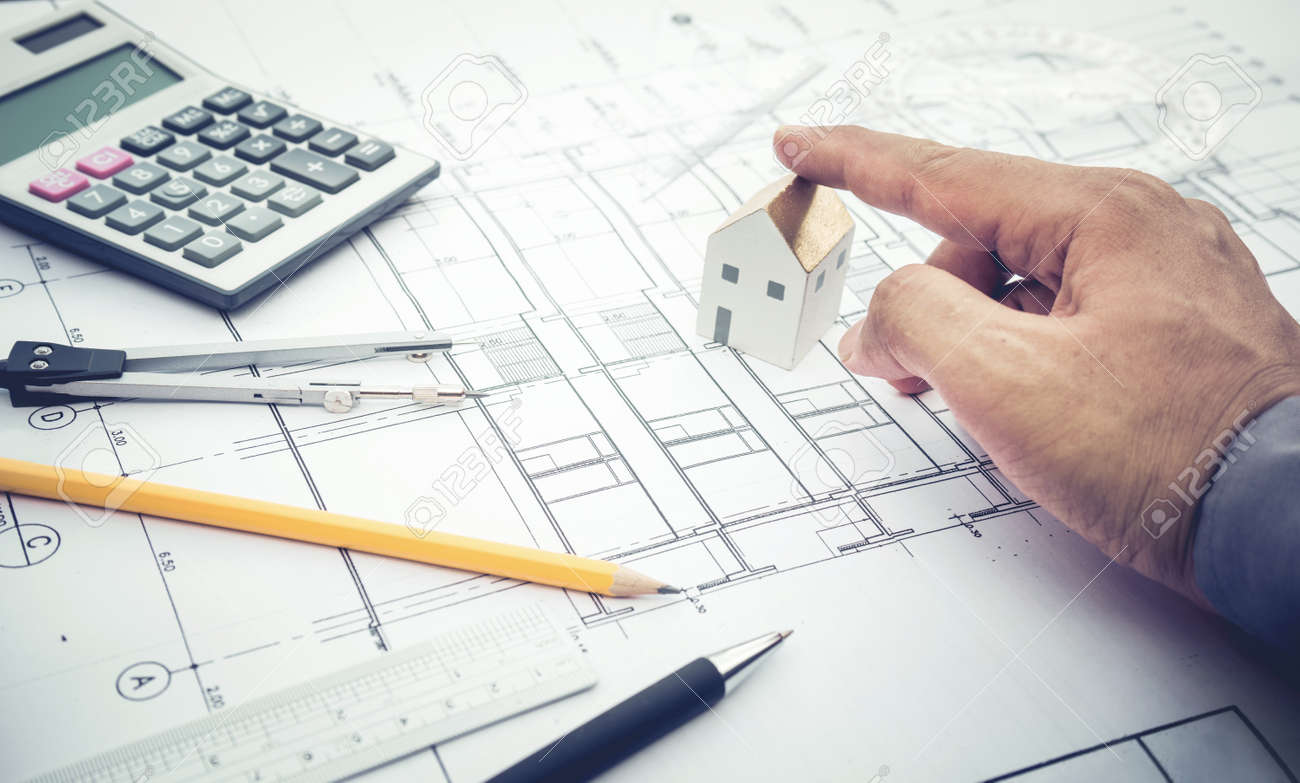 Architect withs mall house model on hand and plan design Concepts