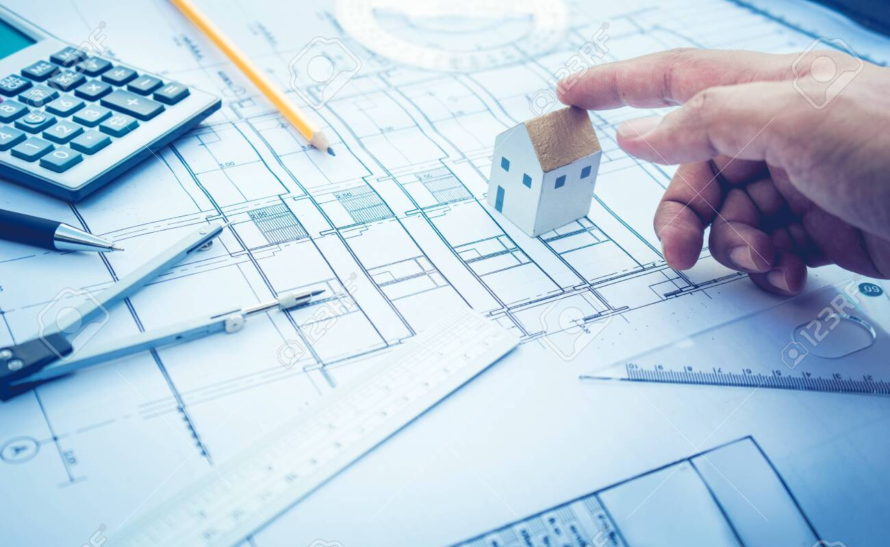 Architect with small house model on hand and plan design Concepts