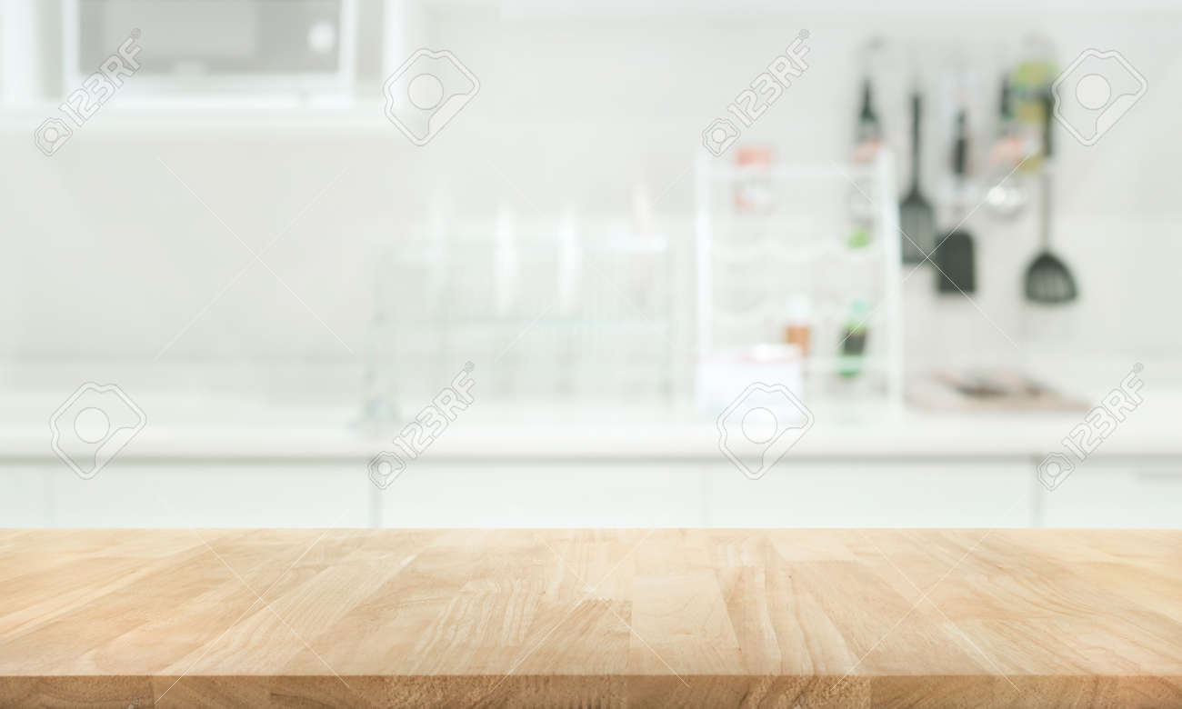 Wood table top on blur kitchen room background .For montage product..