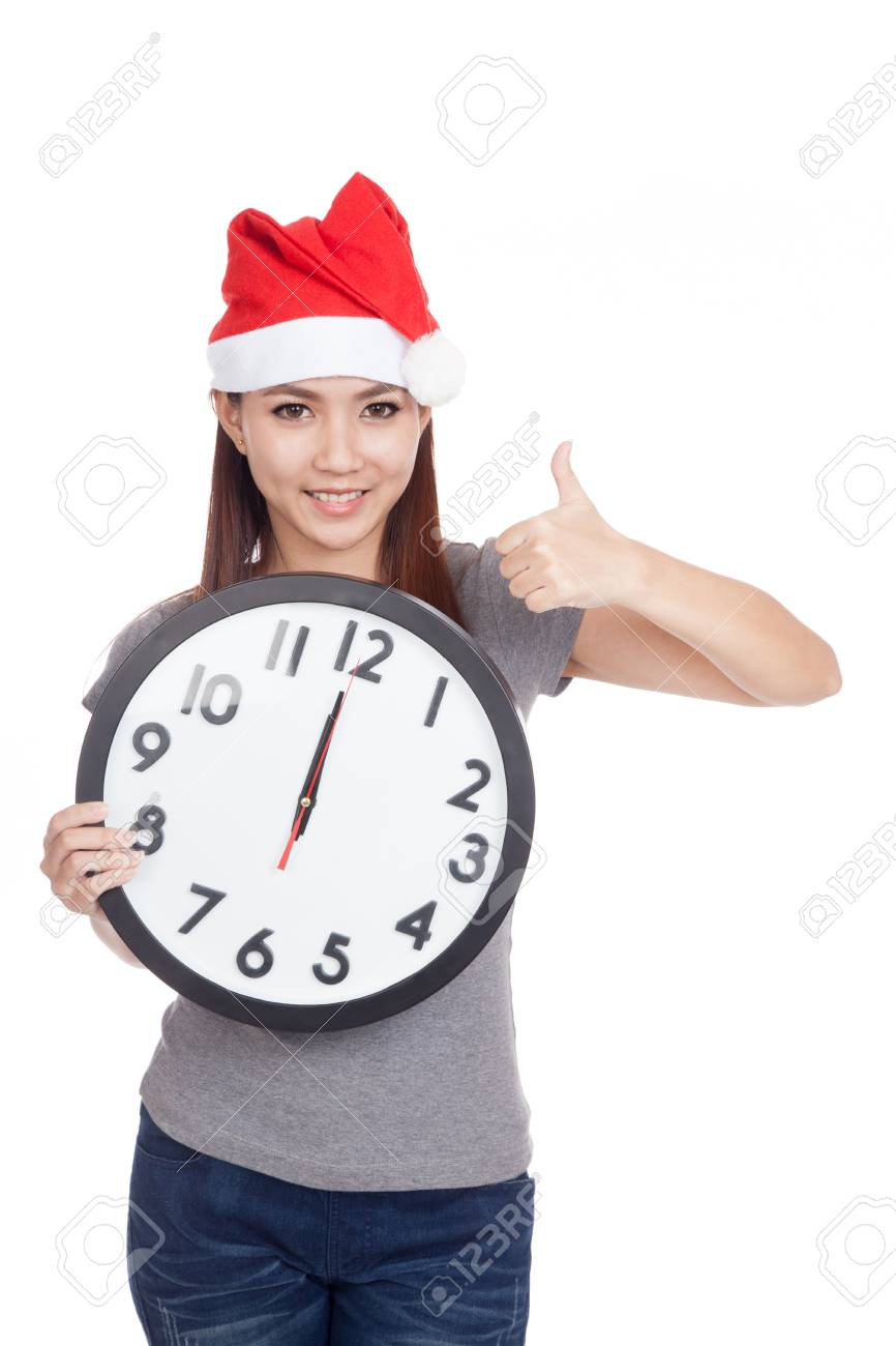 Asian girl with red santa hat and clock show thumbs up isolated on white background - 34515437