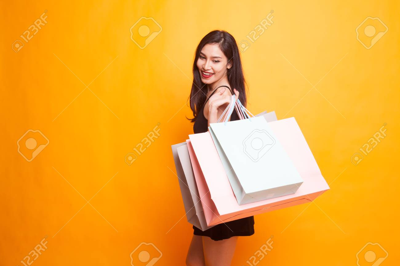 Young Asian woman happy with shopping bag on yellow background - 99895832