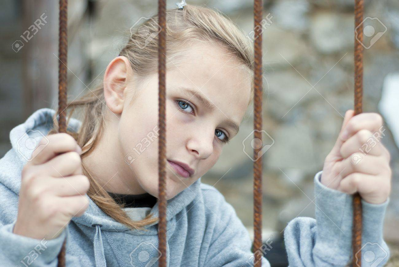 Sad lonely child is behind grid Stock Photo - 16334661
