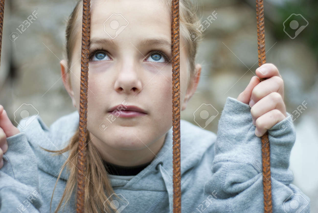 Sad lonely child is behind grid Stock Photo - 16334633