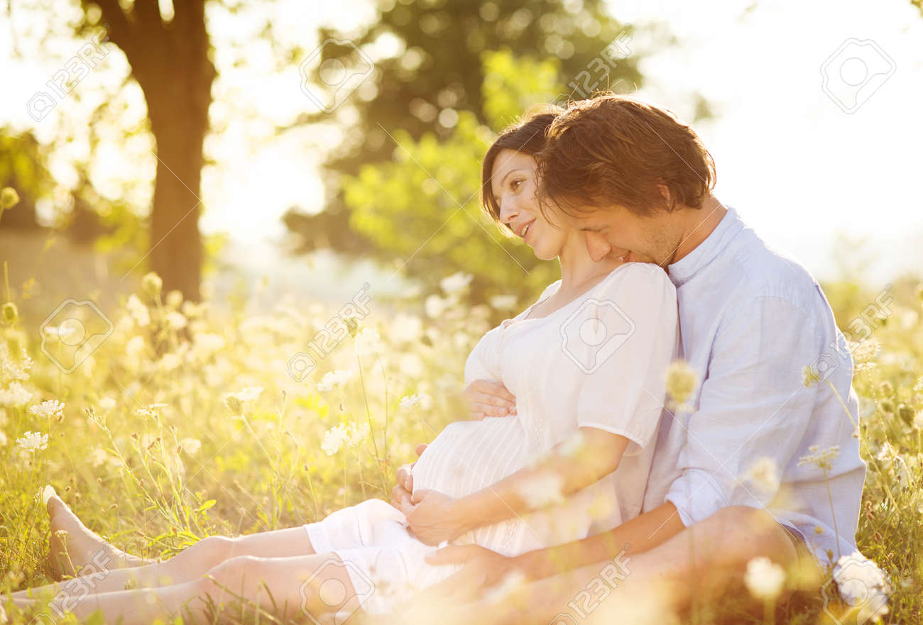 Happy and young pregnant couple hugging in nature Stock Photo - 21471870