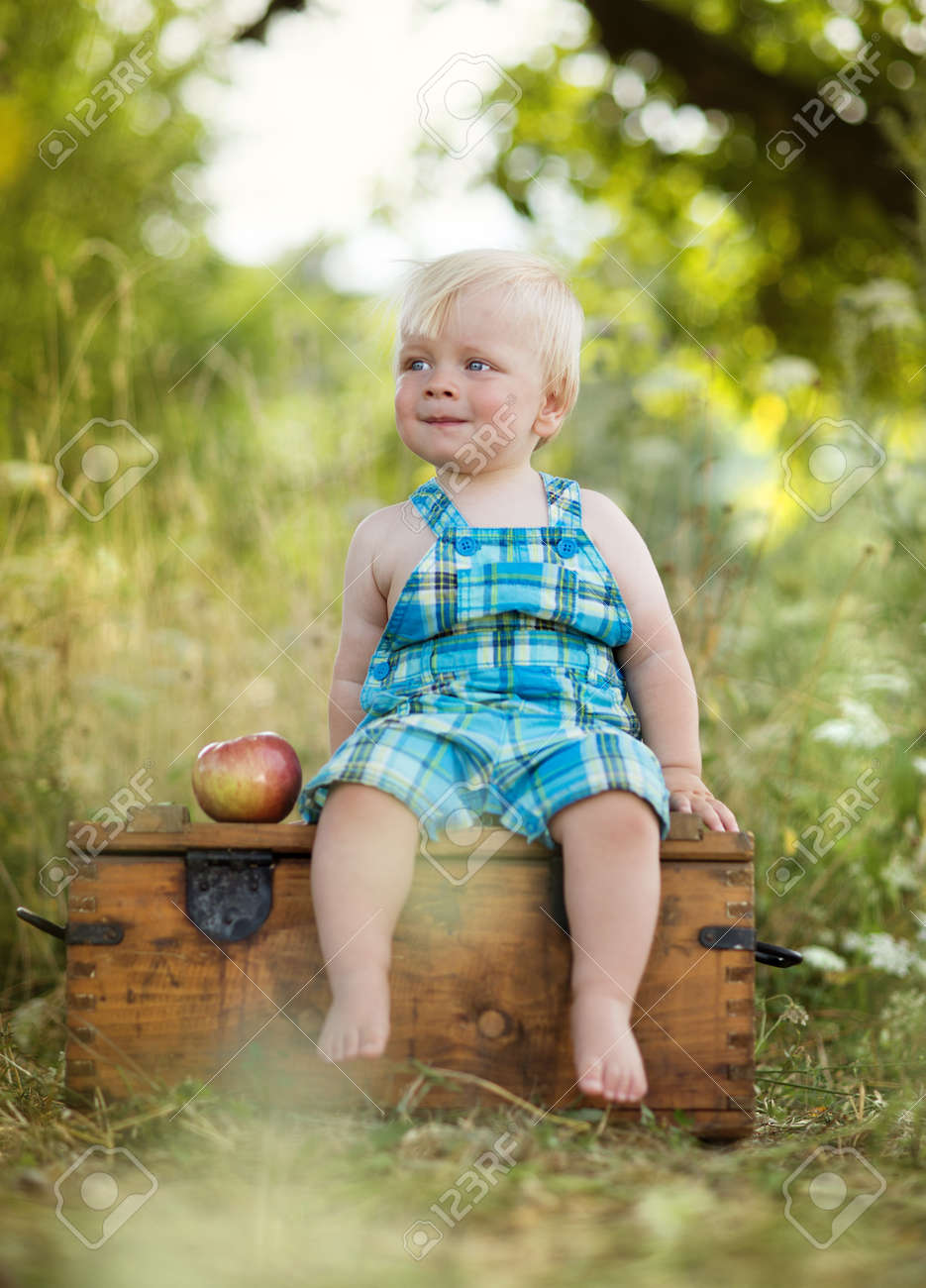 Happy kid playing in a green field Stock Photo - 24258520