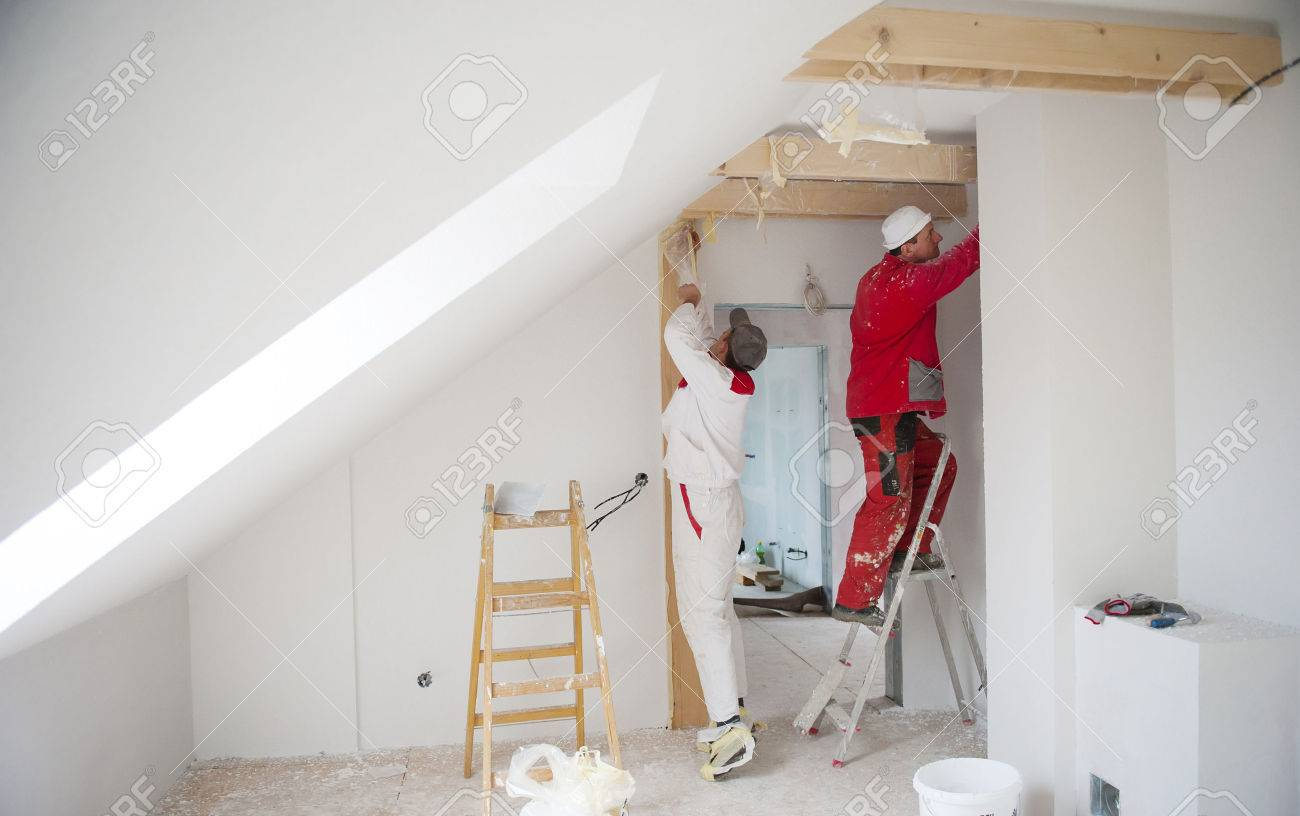 Construction worker is painting the wall in new house - 25184096