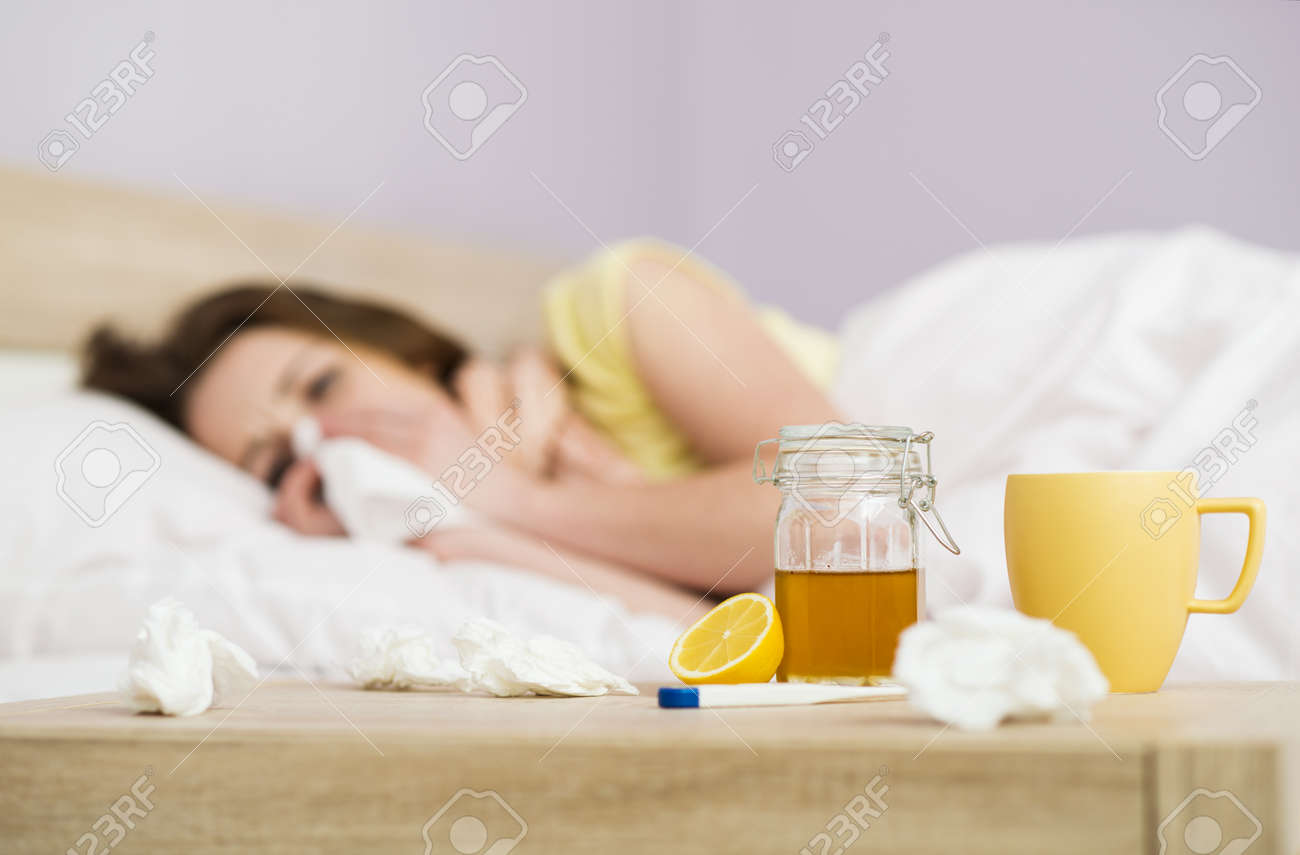 Sick woman lying in bed with high fever  She has cold and flu  In front of her is tea with lemon and honey Stock Photo - 26223874