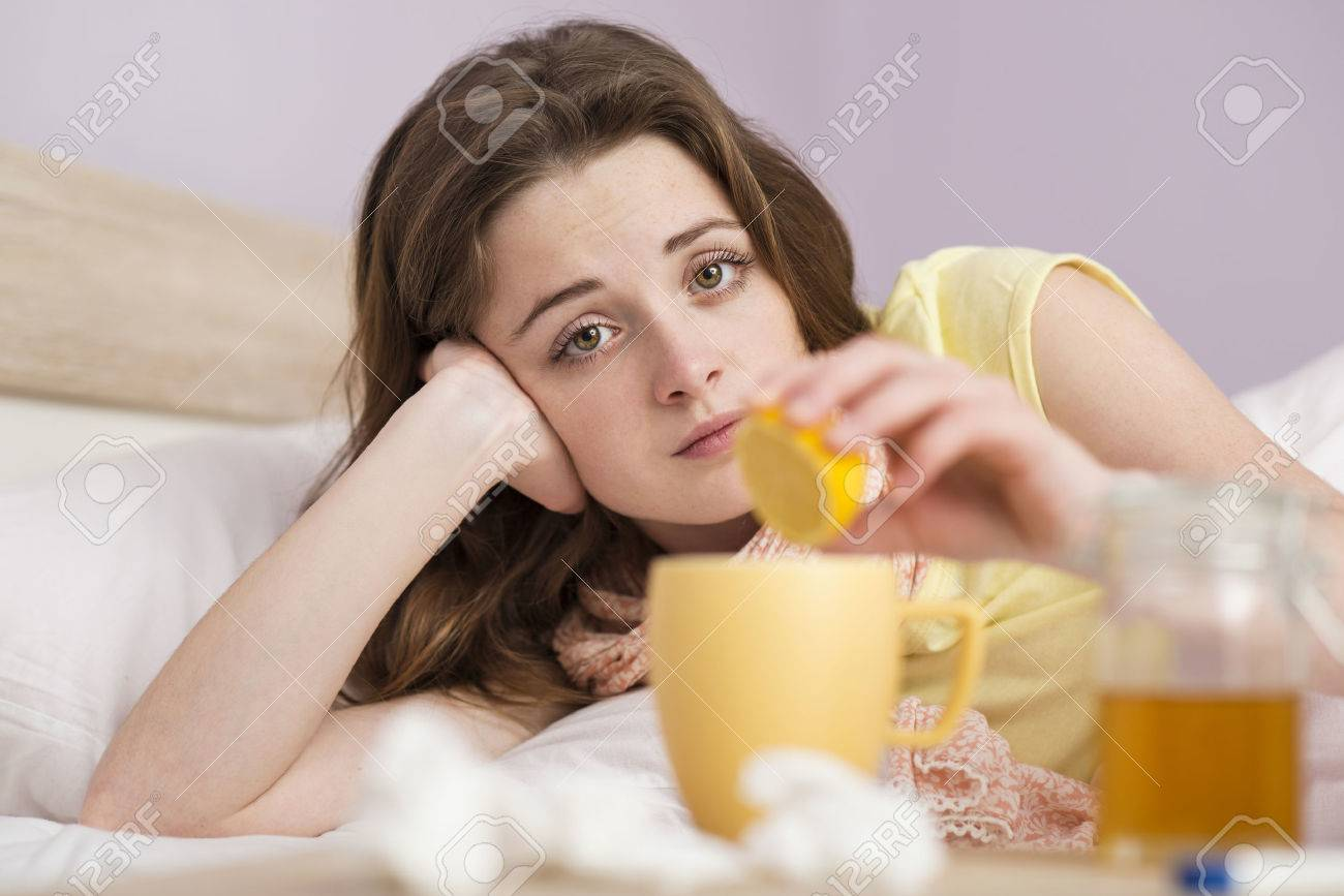 Sick woman lying in bed with high fever  She has cold and flu  She is drinking tea with honey and lemon Stock Photo - 26863979