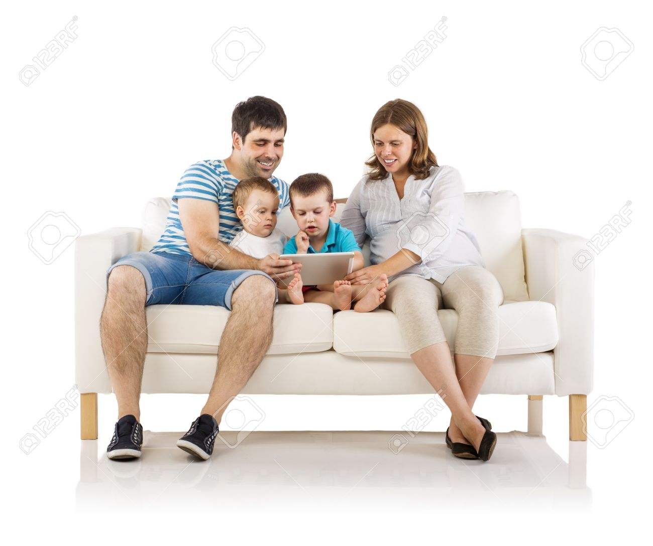 Elegant Portrait Of The Happy Family With Two Children And Pregnant Mother Sitting  On Sofa And Holding