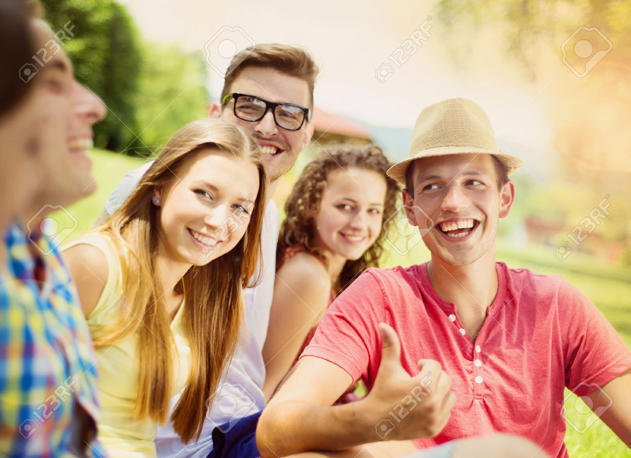 group of young people having fun in park sitting on the grass stock