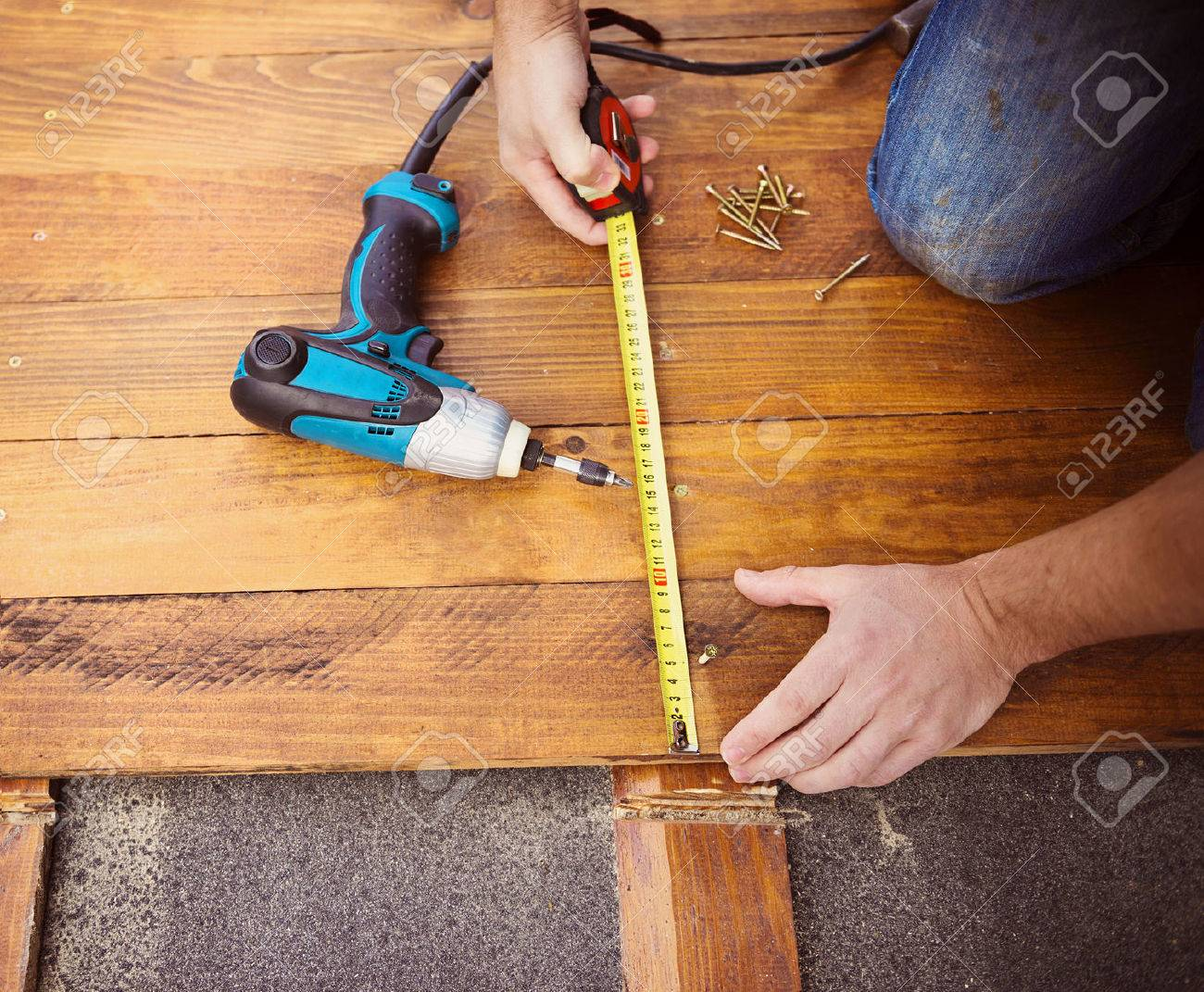 Close Up Of Male Hands Measuring Wood Flooring With Tape Measure Stock Photo 32857230