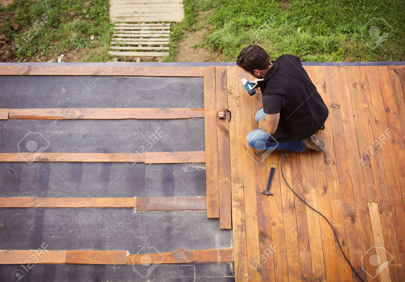 Nice Handyman Installing Wooden Flooring In Patio, Working With Drilling Machine  Stock Photo   32857477