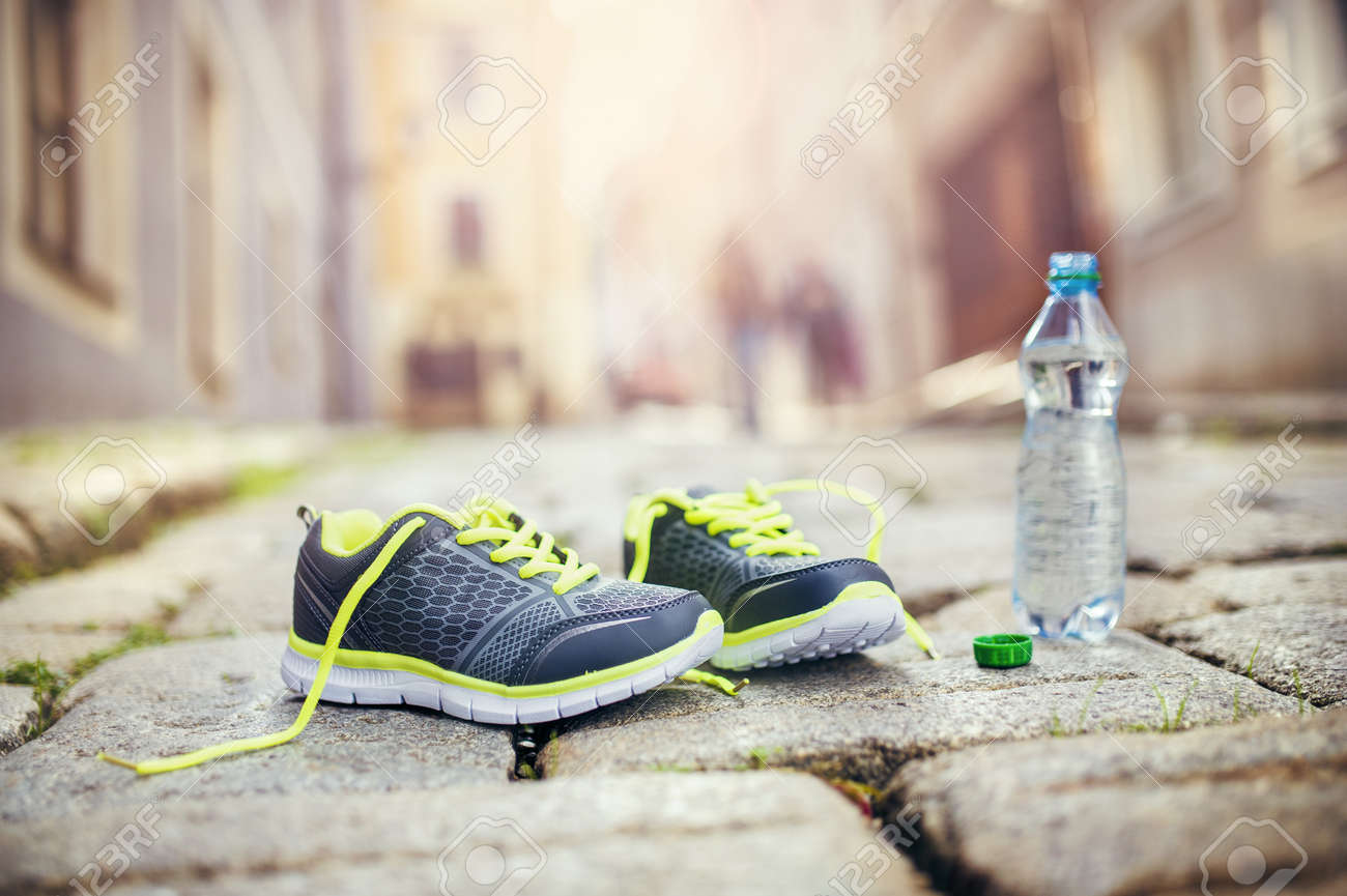 Running Shoes And Bottle Of Water Left