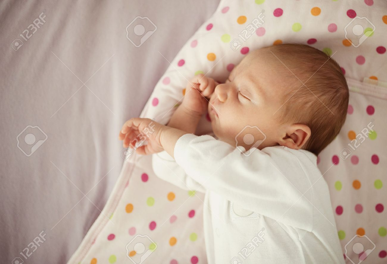 Cute newborn baby girl sleeping in bed at home stock photo 33393252