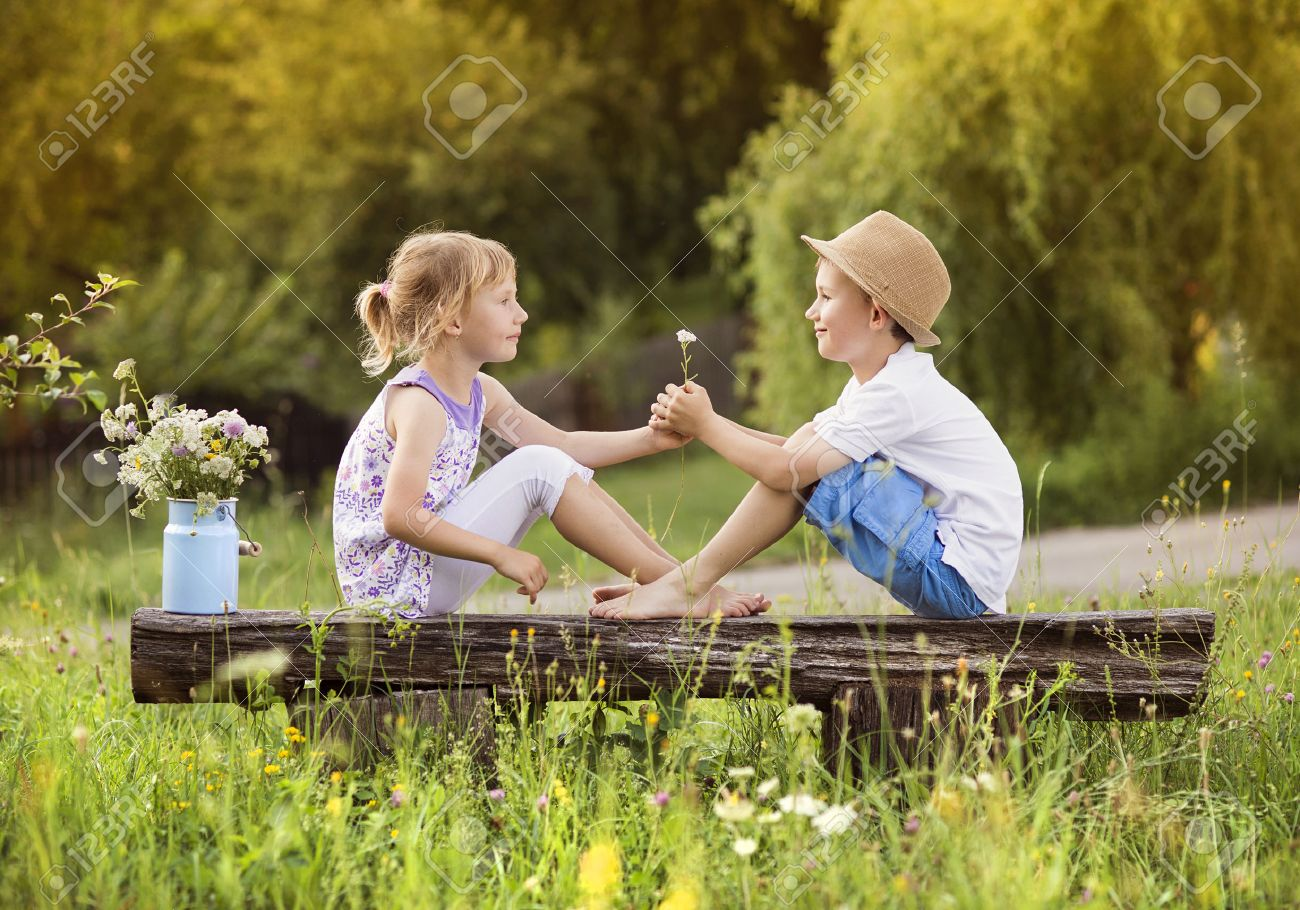cute boy and girl in love. they sitting on bench at sunset. stock