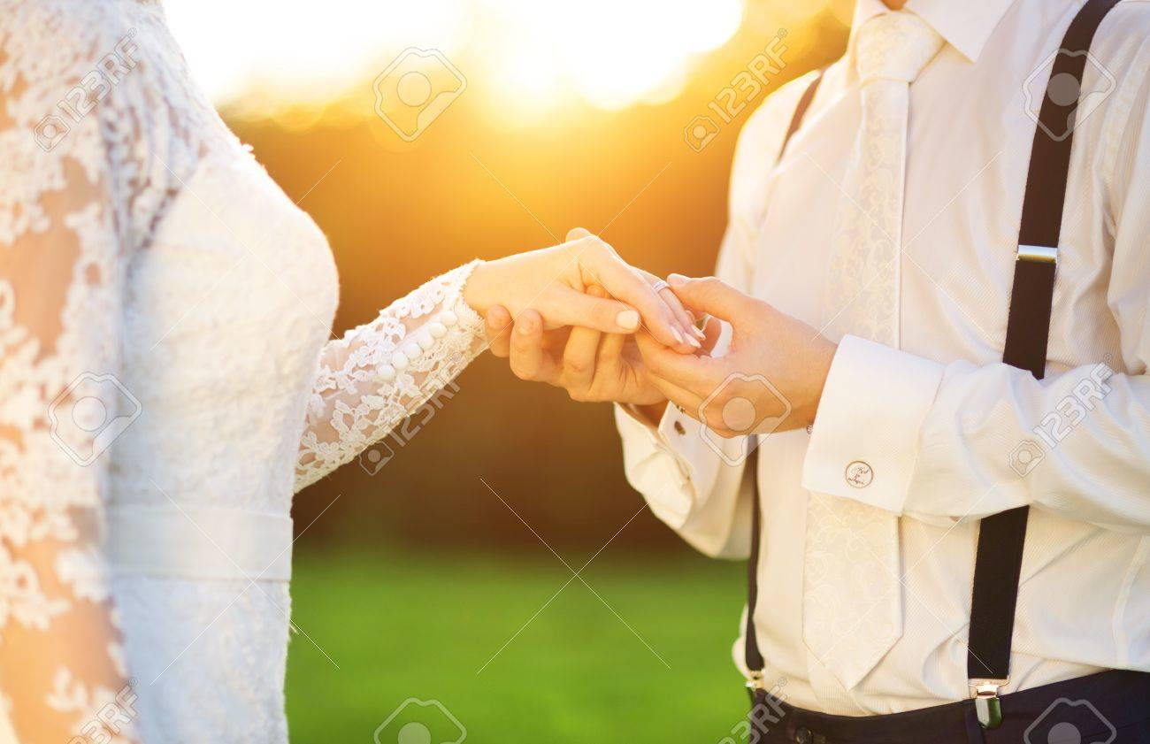 Young wedding couple holding hands as they enjoy romantic moments outside on a summer meadow - 35548919