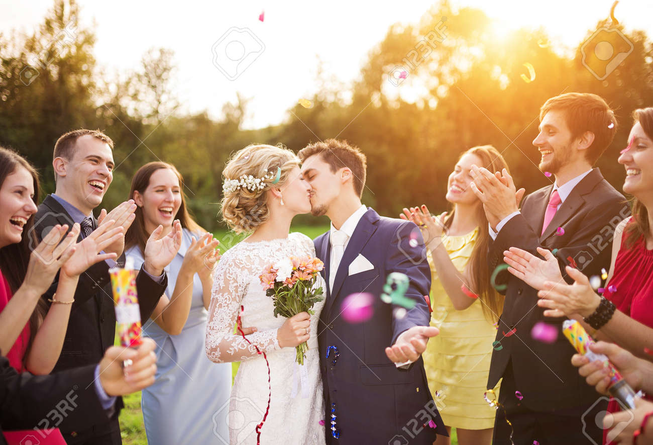 Full length portrait of newlywed couple and their friends at the wedding party showered with confetti in green sunny park - 35800941