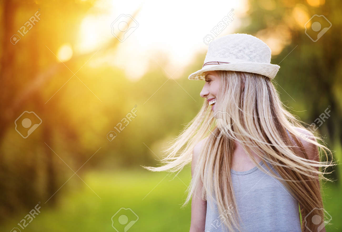 Attractive young woman enjoying her time outside in park with sunset in background. - 35800973
