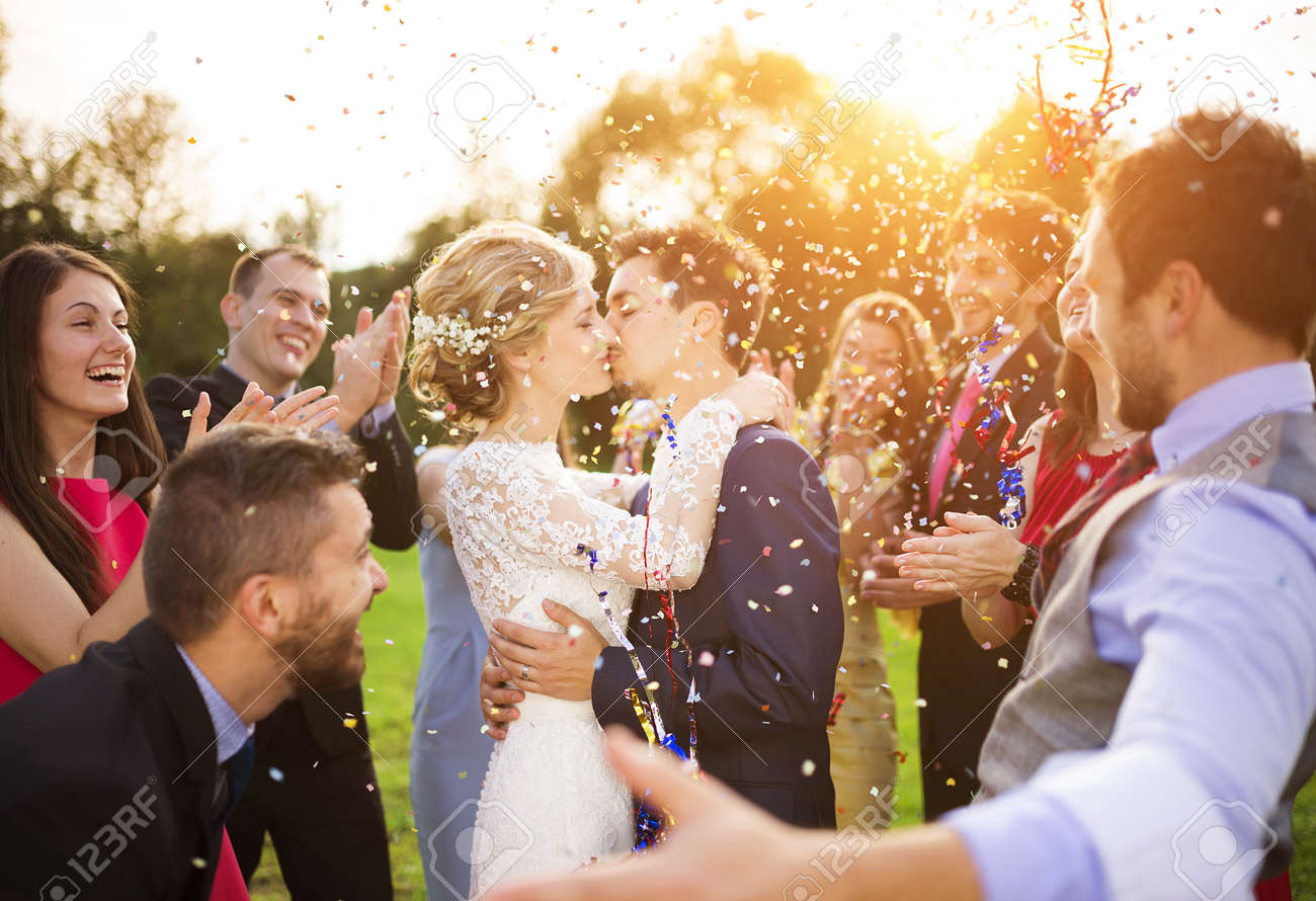 Full length portrait of newlywed couple and their friends at the wedding party showered with confetti in green sunny park Stock Photo - 35800989