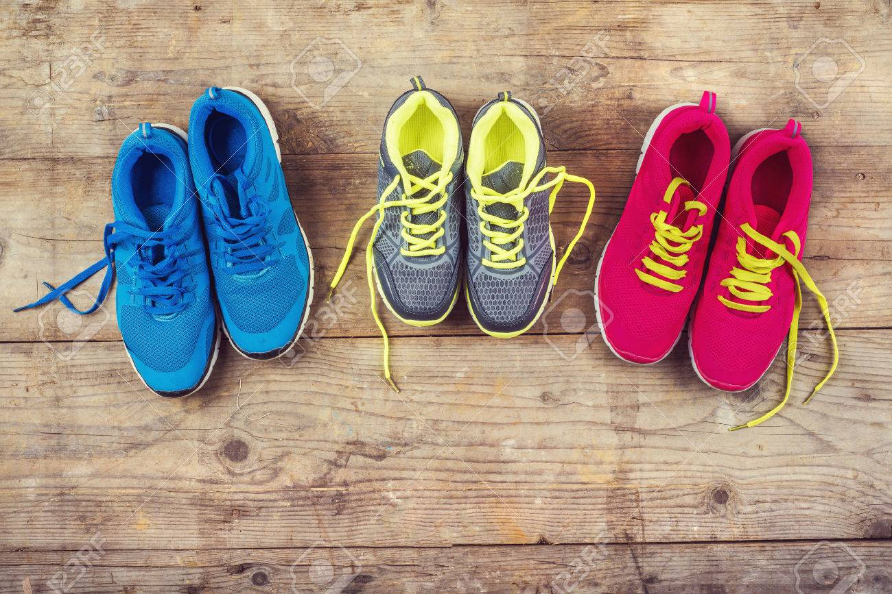 Various pairs of colorful sneakers laid on the wooden floor background - 36096506