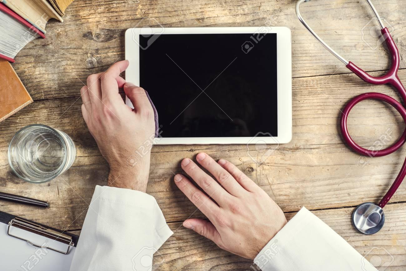 Mains de médecin méconnaissable écrit sur une tablette bois fond
