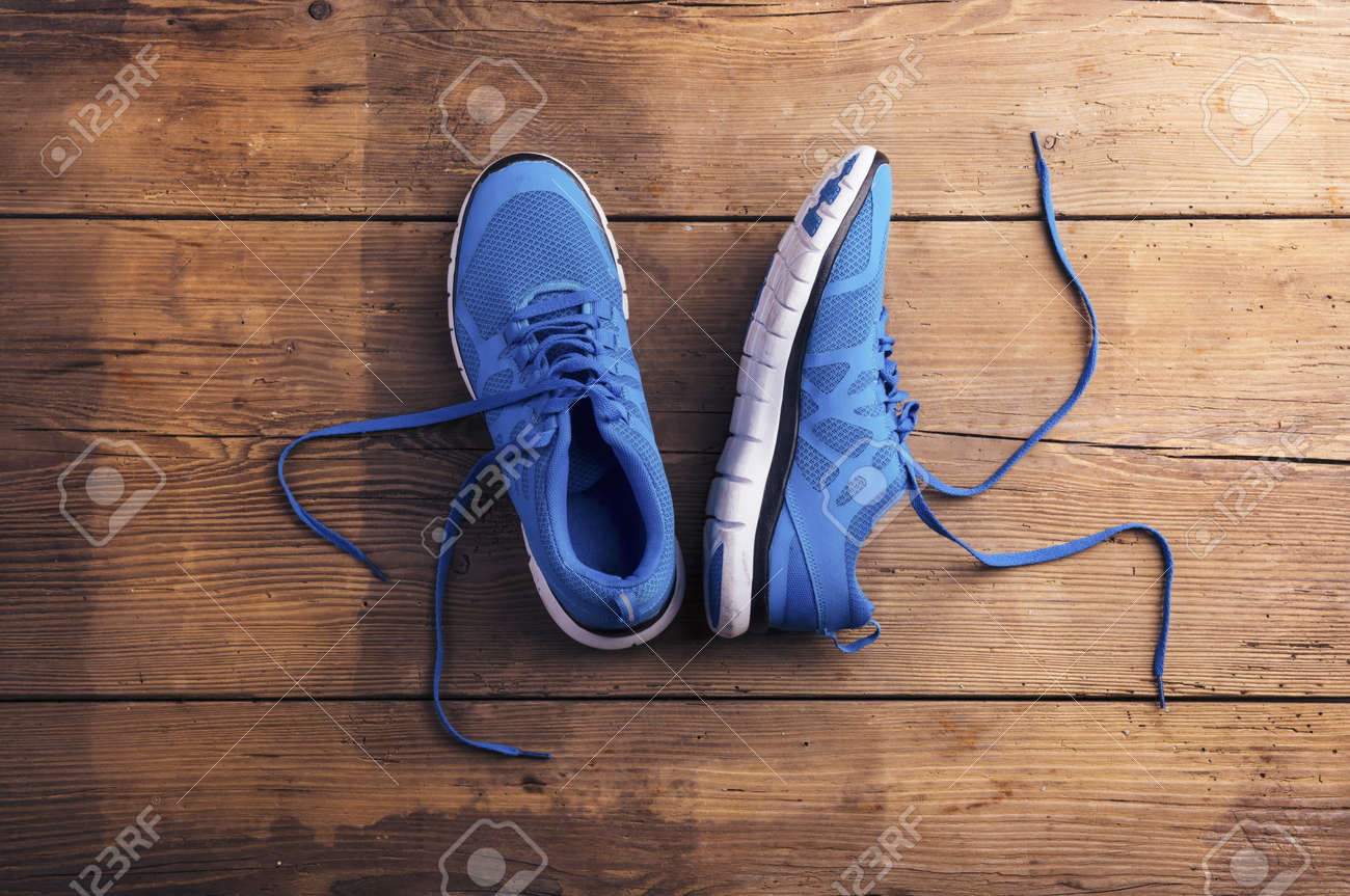 Pair of blue running shoes laid on a wooden floor background - 38905988