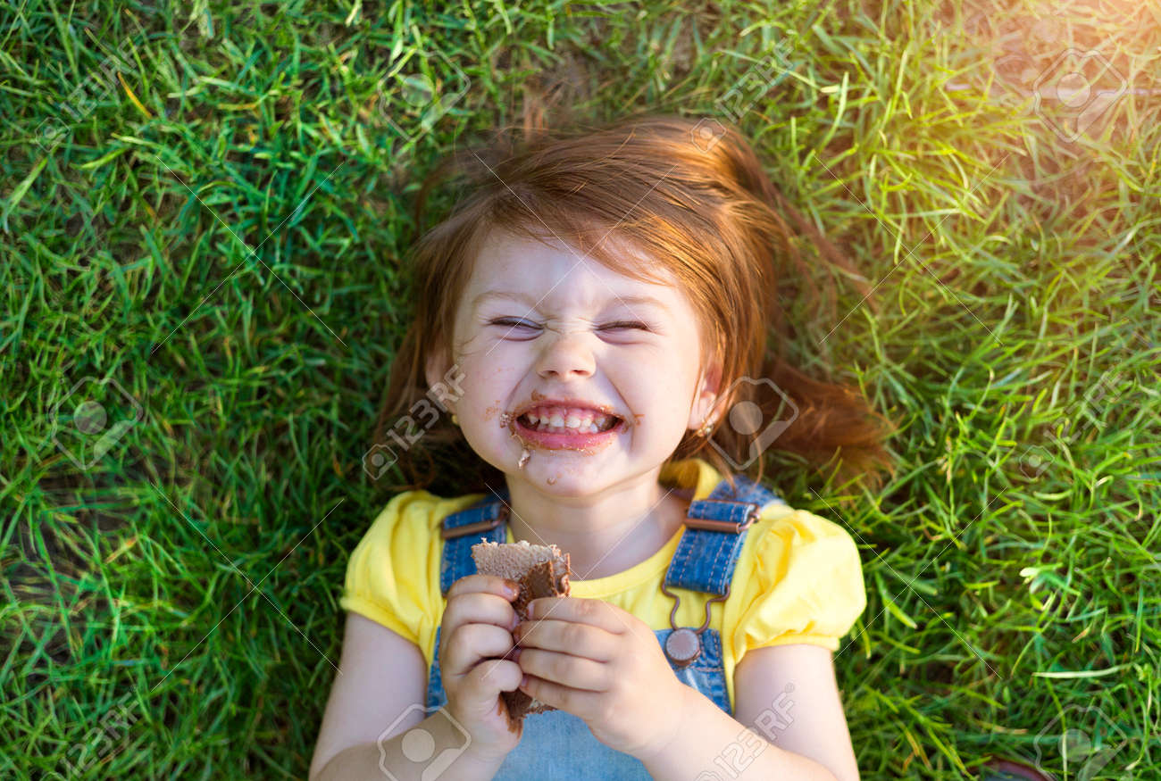 Cute Little Girl With Chocolate Face Lying On A Grass Stock Photo ...
