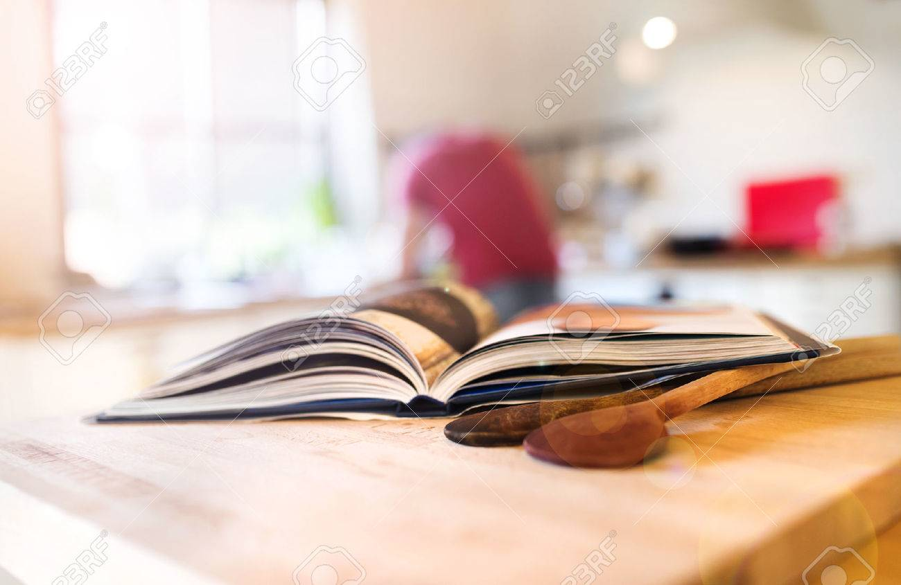 cook book laid on a kitchen table with two wooden spoons stock