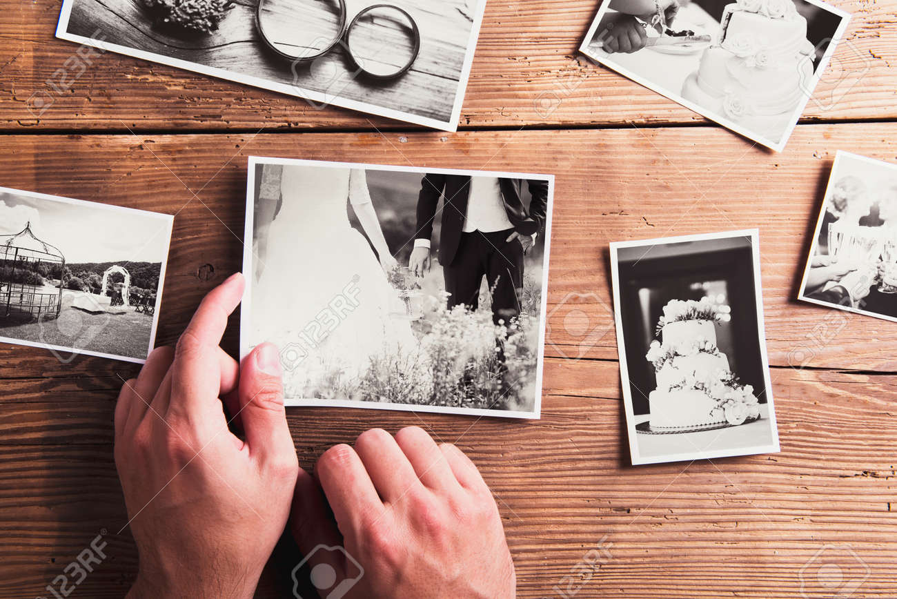 Wedding photos laid on a table. Studio shot on wooden background. Stock Photo - 47169629