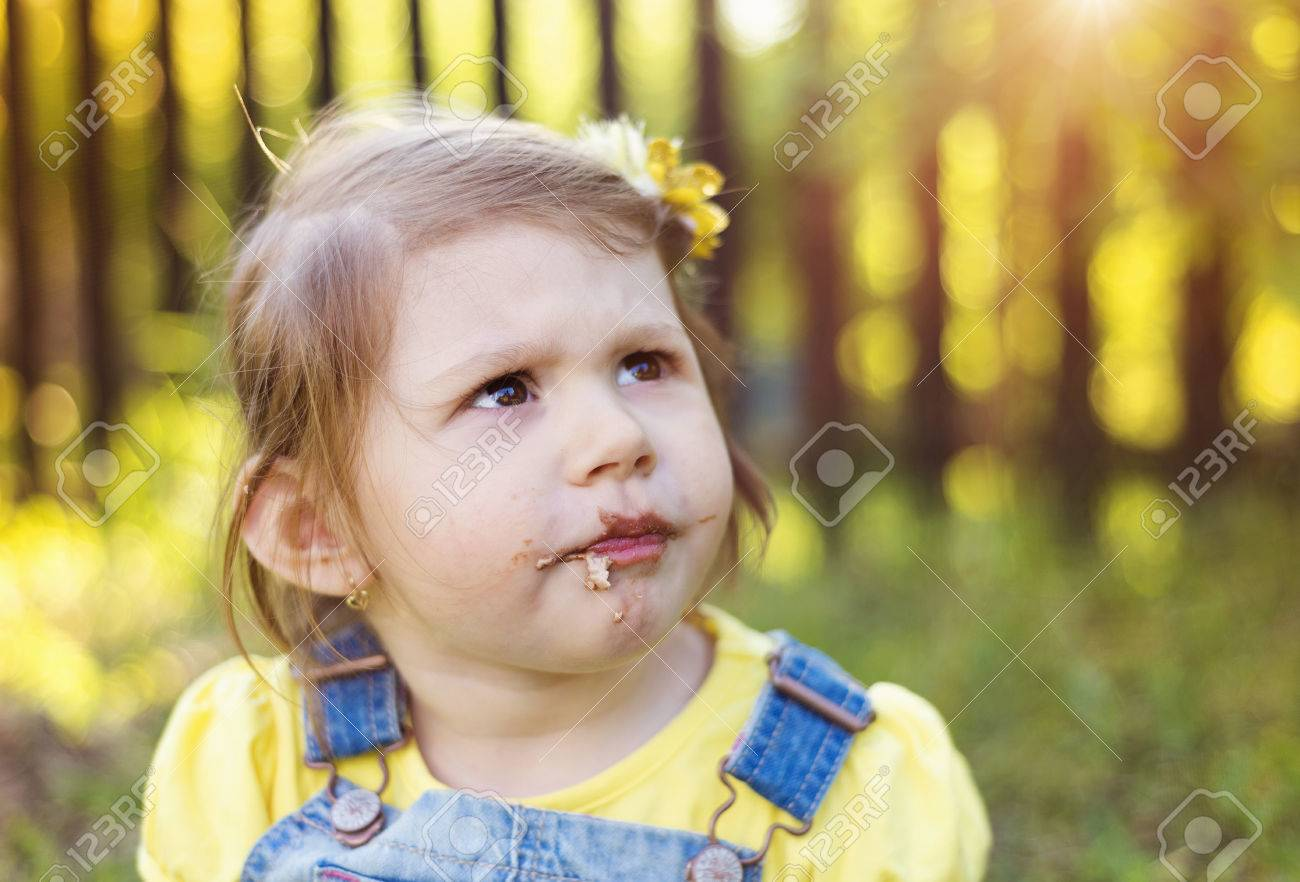 Cute Little Girl With Chocolate Face Sitting On A Grass Stock ...