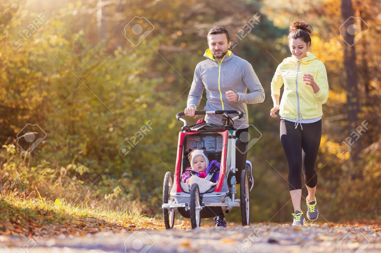 Beautiful young family with baby in jogging stroller running outside in autumn nature - 50204808
