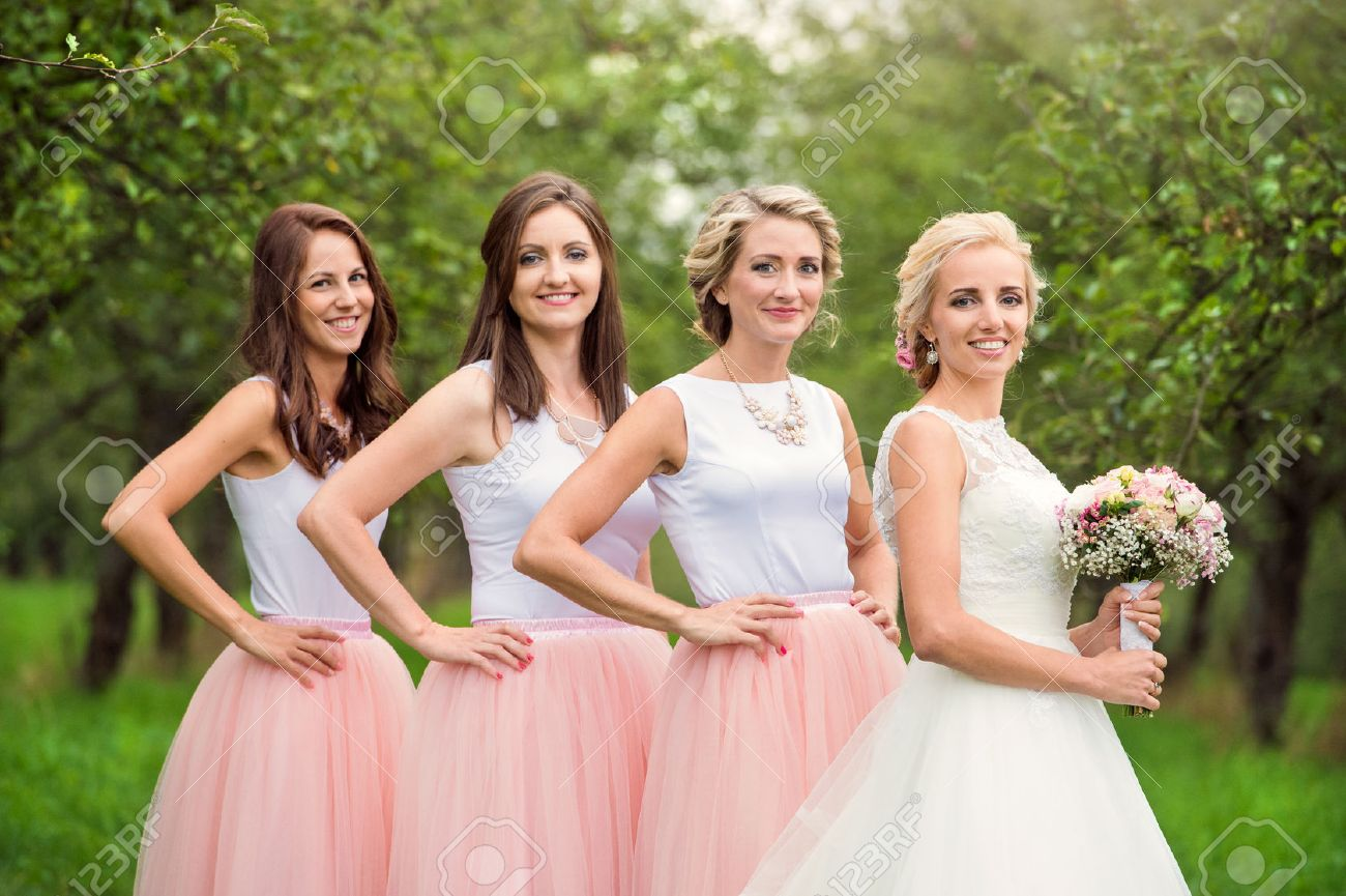 Beautiful young bride with her bridesmaids outside in nature - 50476490
