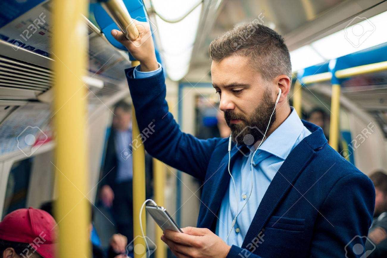 Serious businessman with headphones travelling to work. Standing inside underground wagon, holding handhandle. - 53380343