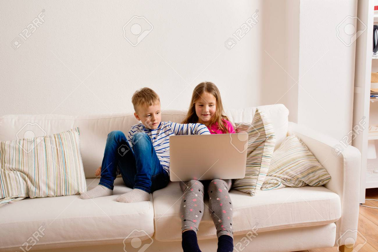Little Girl And Boy Sitting On Sofa With A Laptop Computer At Home. Happy  Children