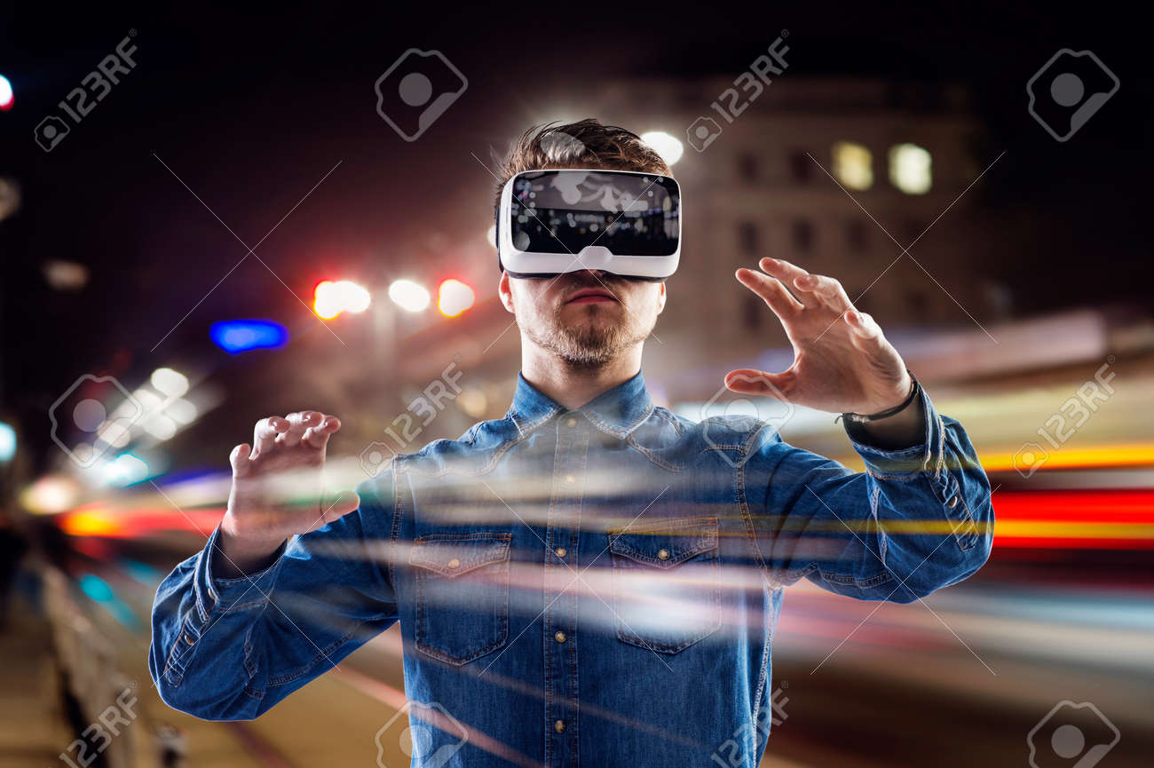 Double exposure of man wearing virtual reality goggles and night city Stock Photo - 53460575