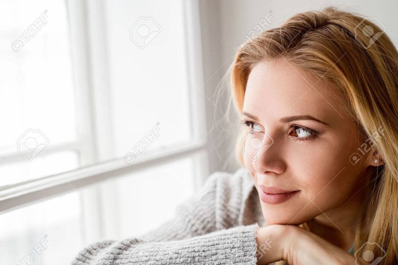Beautiful blond woman sitting on window sill, looking out of window - 54065285