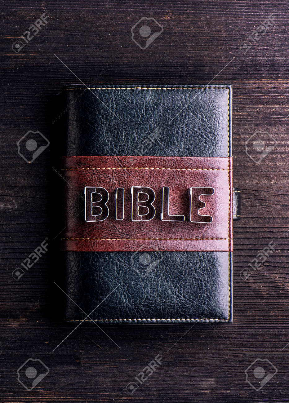 bible in leather book cover laid on old wooden table sign made