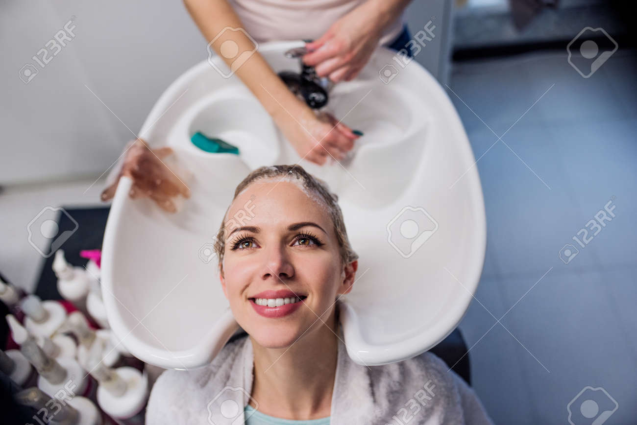 Unrecognizable professional hairdresser washing hair to her beautiful client. Young woman in a hair salon - 55745755