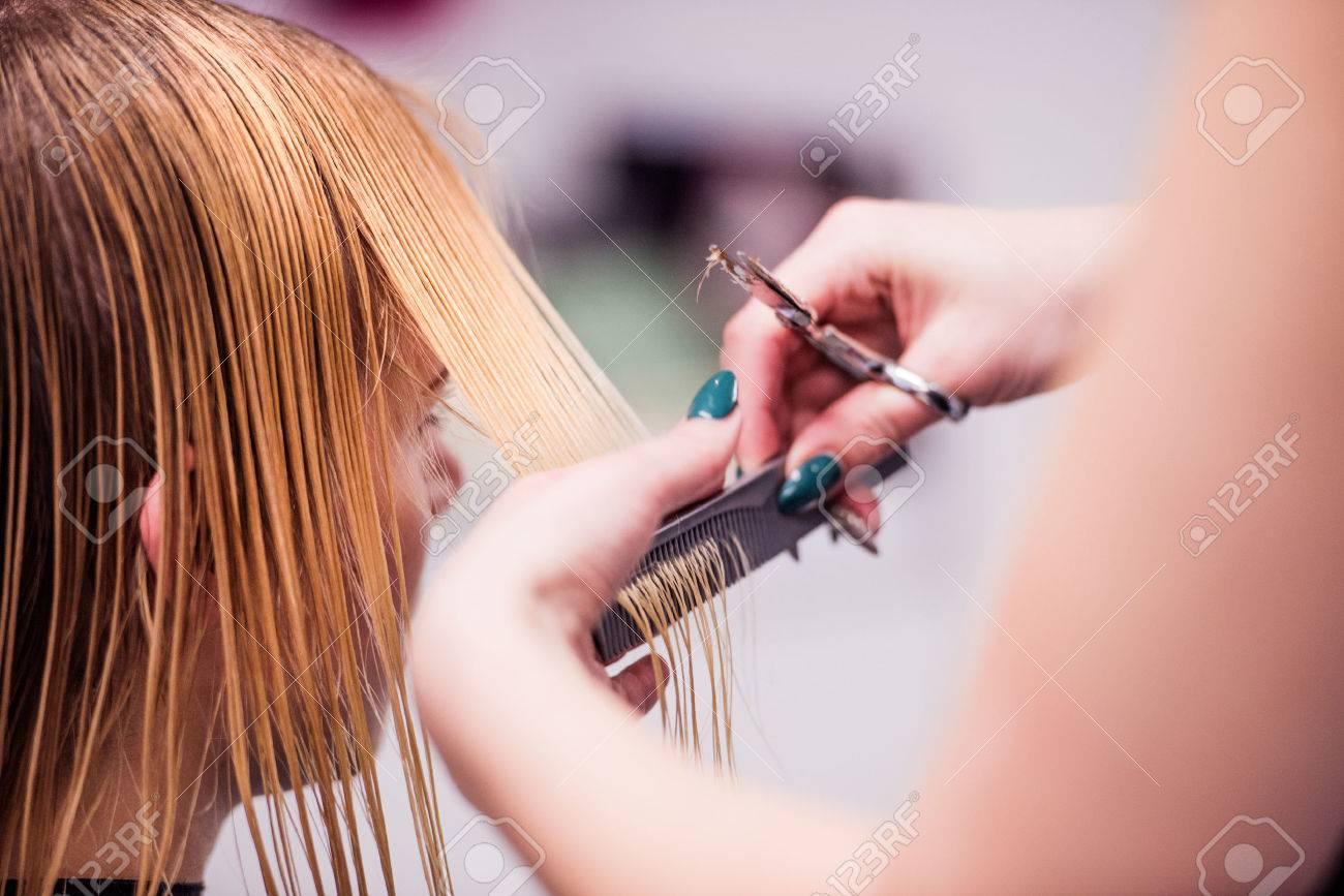 Mains de coiffeur professionnel méconnaissable coupe les cheveux de son client, donnant une nouvelle coupe de cheveux à la clientèle féminine. Banque d'images - 55745800