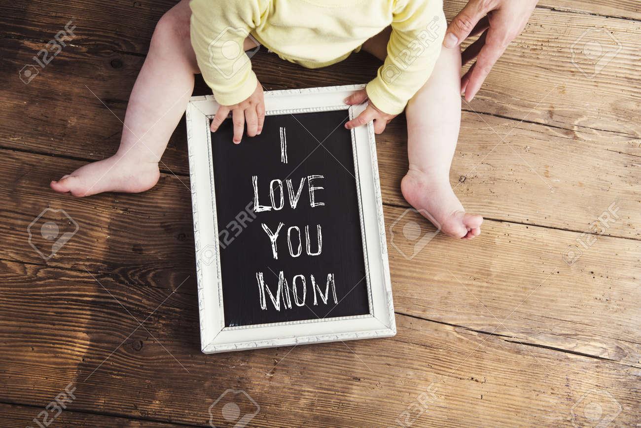 Composition du jour des mères. Bébé non reconnaissable en tissu jaune tenant un signe de craie dans un cadre photo. Studio tiré sur un fond en bois. Banque d'images - 55746202