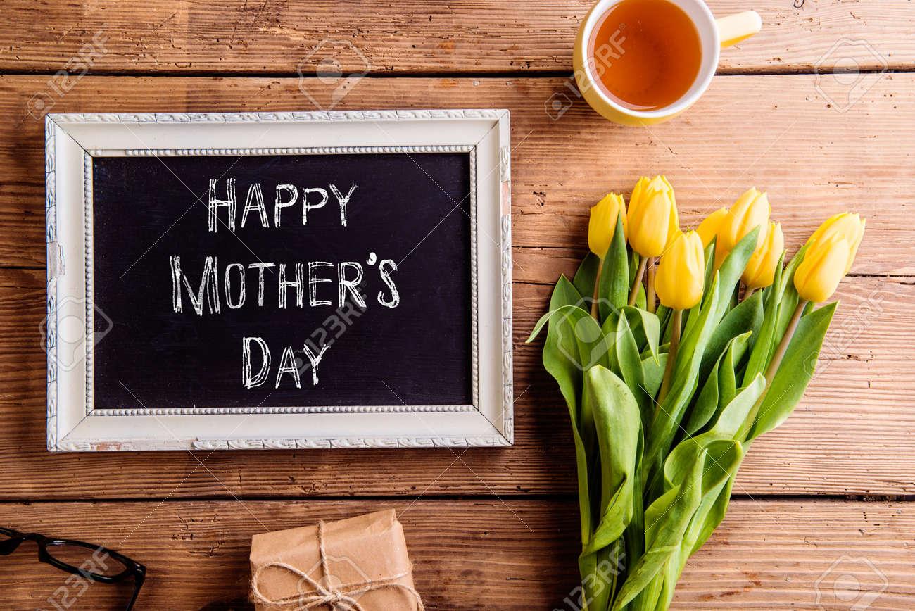 Composition du jour des mères. Cadre avec panneau à craie, bouquet de tulipes jaunes, cadeau et tasse de thé. Studio tiré sur un fond en bois. Banque d'images - 55840071