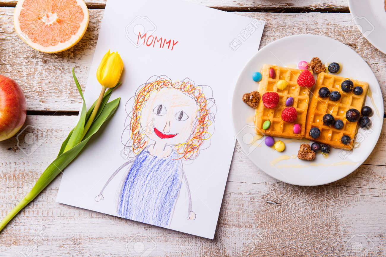 Mothers day composition. Childs drawing of her mother, yellow tulip and breakfast waffles with fruit. Studio shot on wooden background. Banque d'images - 55840137