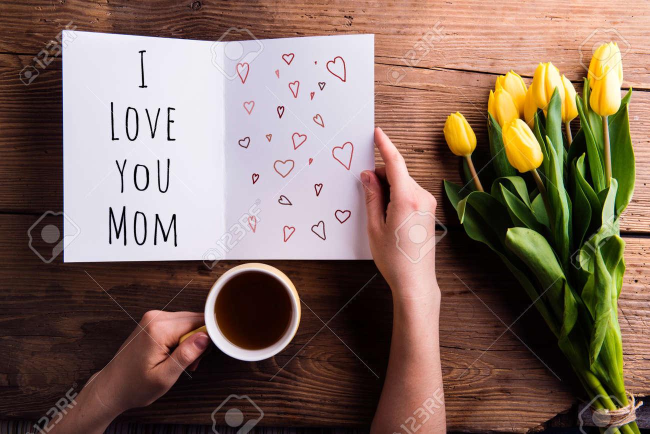 Les mères composition de jour. Mains de femme tenant méconnaissable carte de voeux avec je vous aime signe maman et tasse de café. Bouquet de tulipes jaunes. Tourné en studio sur fond de bois. Banque d'images - 56193274