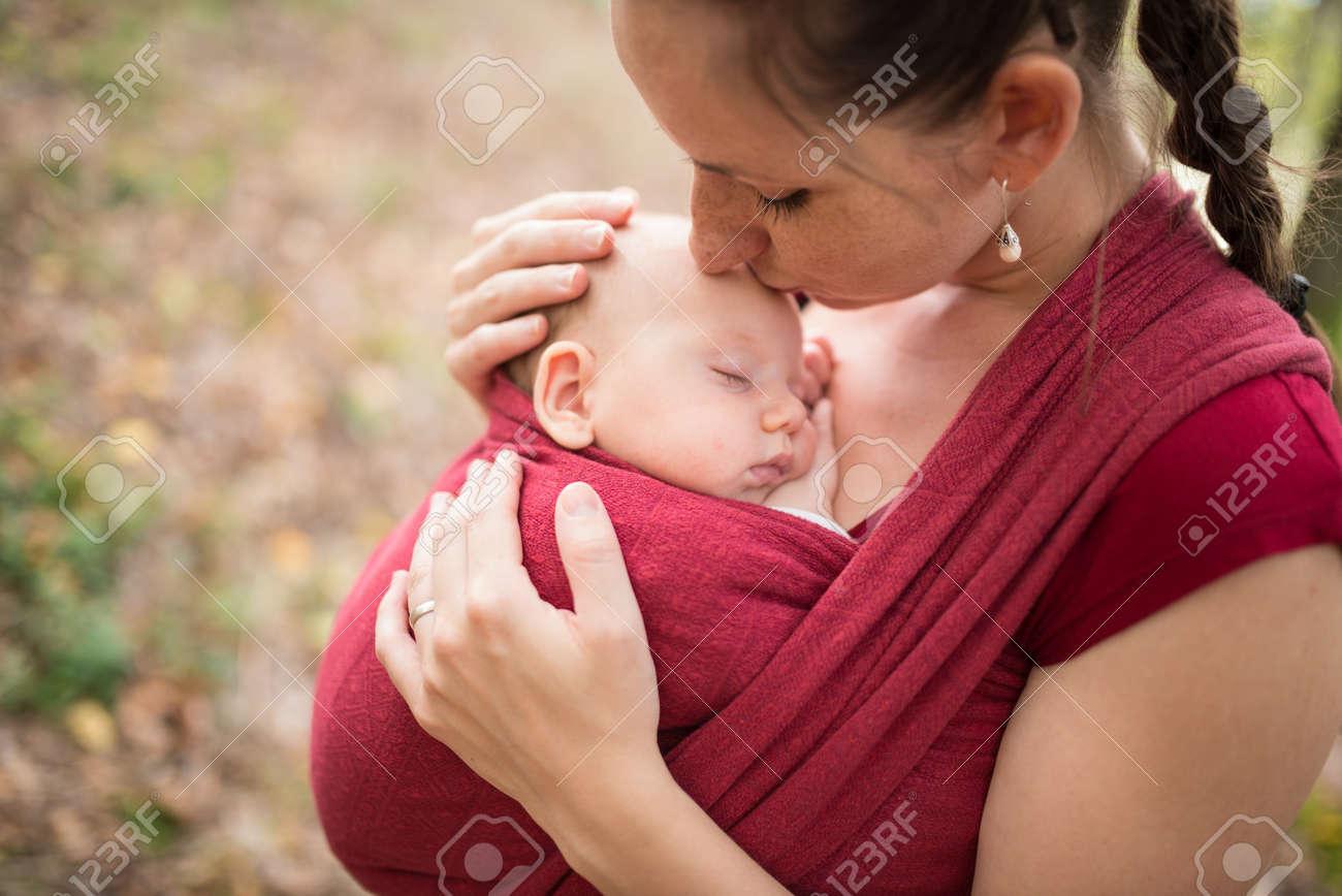 Mère portant son bébé fille mignonne dans fronde, en l'embrassant, en dehors de la nature en automne Banque d'images - 56193981