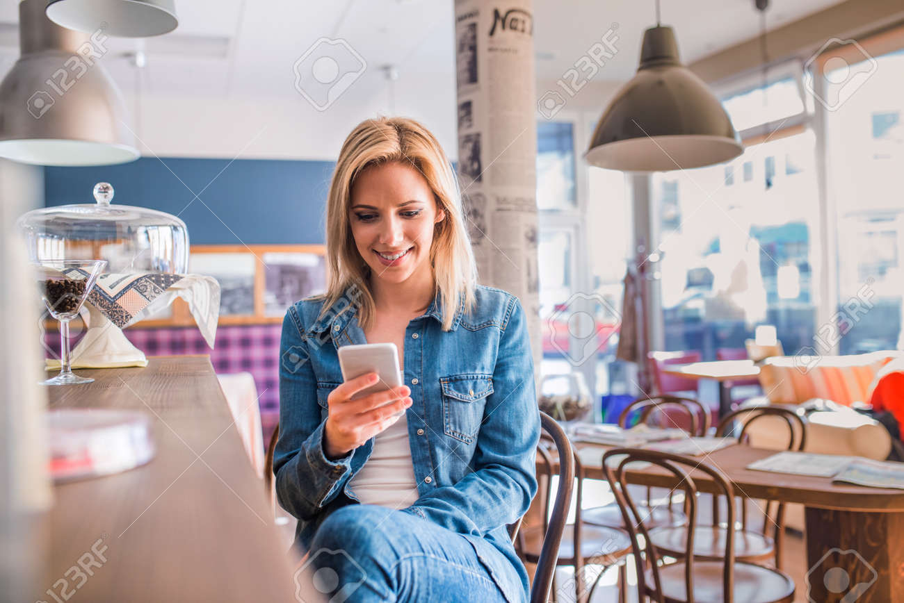 Blond woman in denim shirt sitting at the bar in modern city cafe, holding a smart phone, texting - 56194129