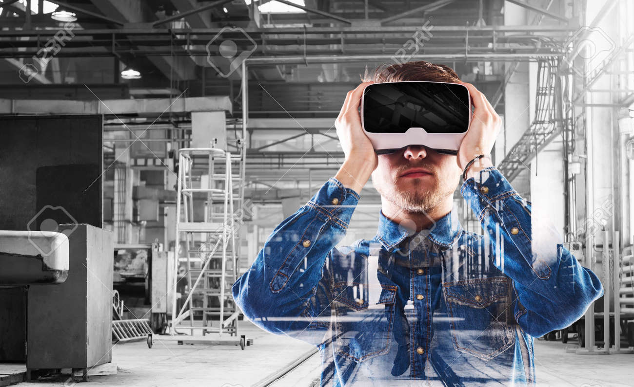Hipster man in denim shirt wearing virtual reality goggles. Welding factory. - 56620830