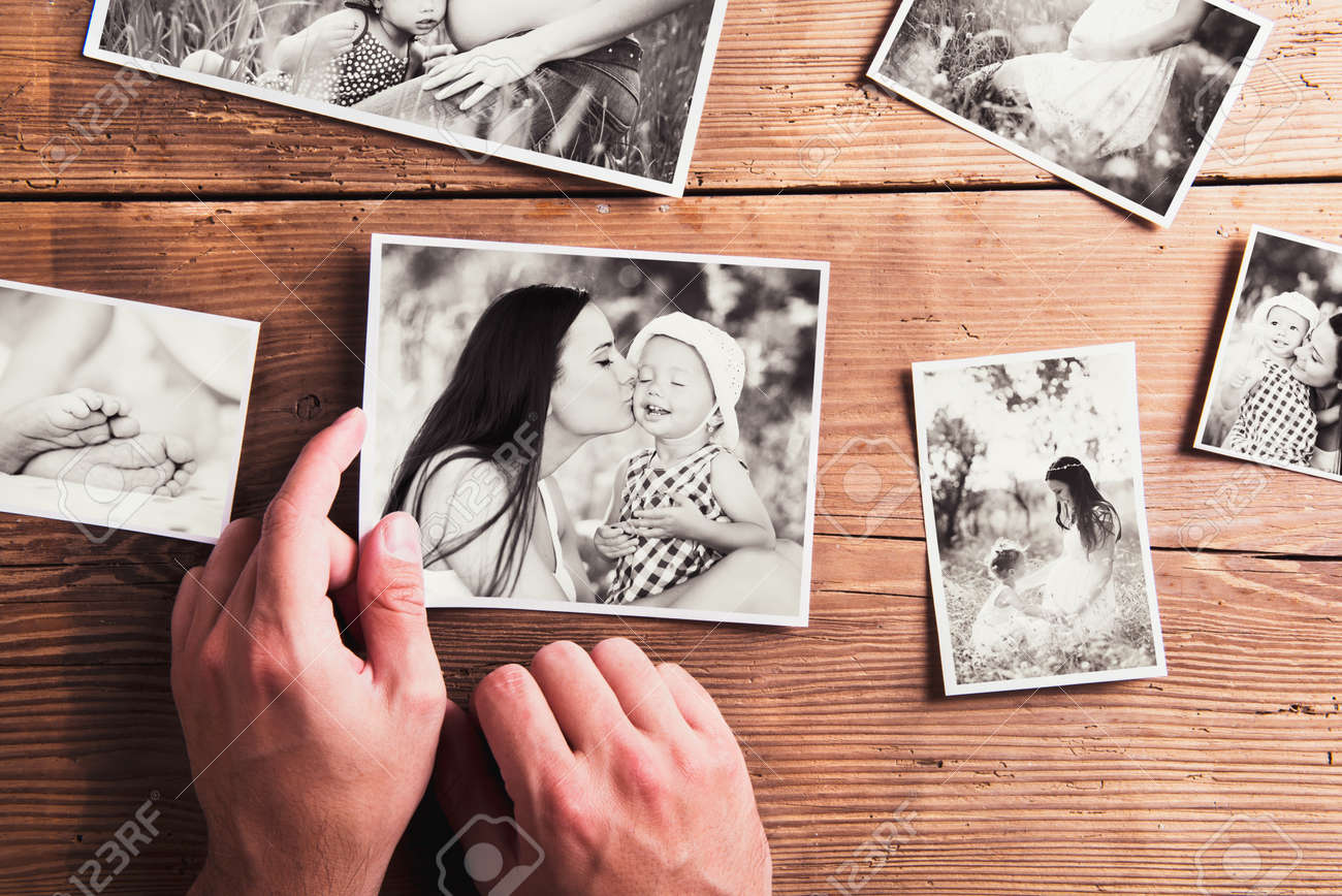 Mothers day composition. Hands of unrecognizable man holding  black-and-white photo. Studio shot on wooden background. Banque d'images - 56620833