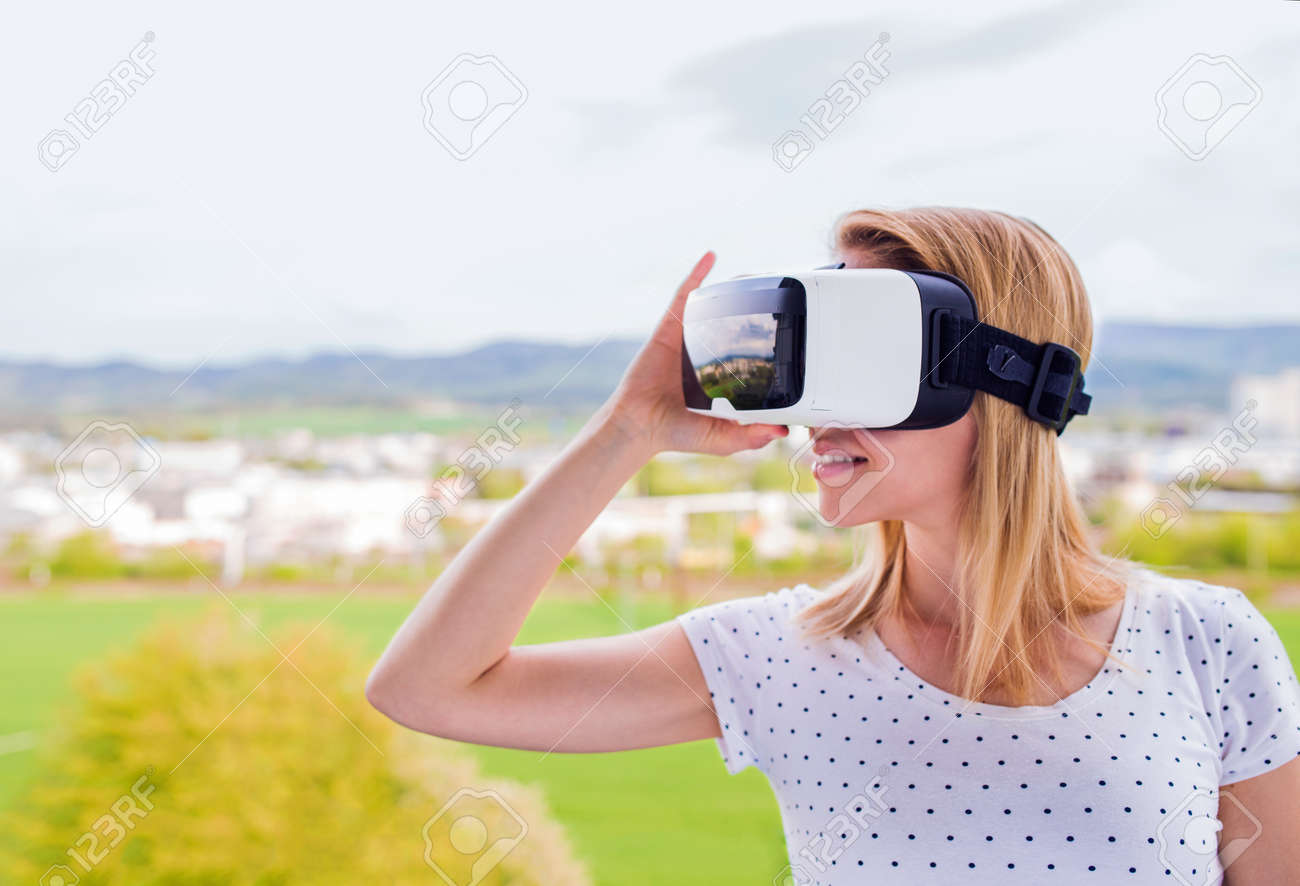 Virtual Reality Keuken : Blond woman wearing virtual reality goggles standing in a kitchen